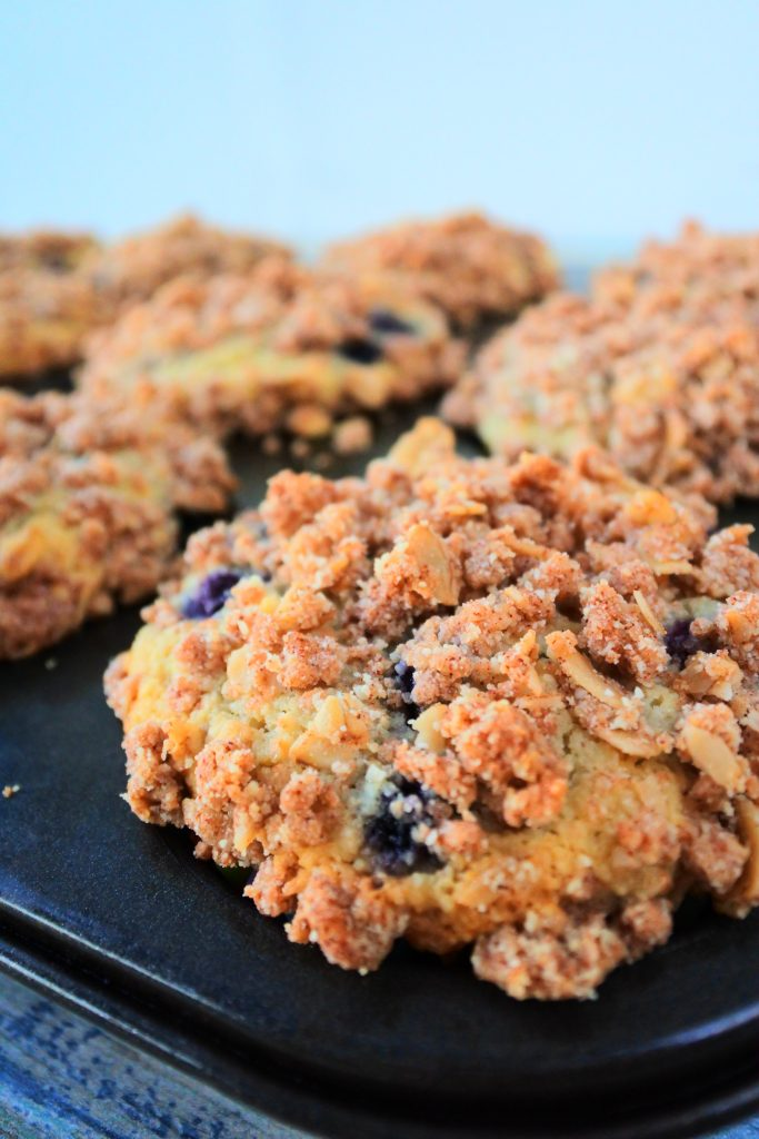 A close up image of blueberry streusel muffins fresh out of the oven