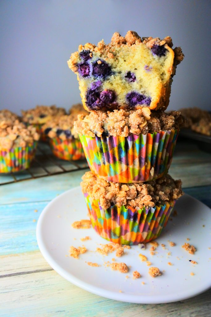 An image of a stack of blueberry streusel muffins with a bite taken out of the top muffin and more muffins on a cooling rack in the background