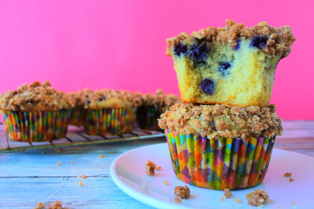An image of two stacked blueberry streusel muffins with the top muffin missing a bite and a cooling rack with more muffins in the background