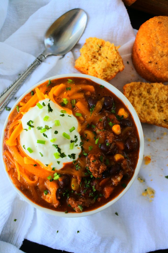 An overhead image of a bowl of kitrusy's chili con carne topped with cheese, sour cream and chives with a spoon and cornmeal muffins on the side