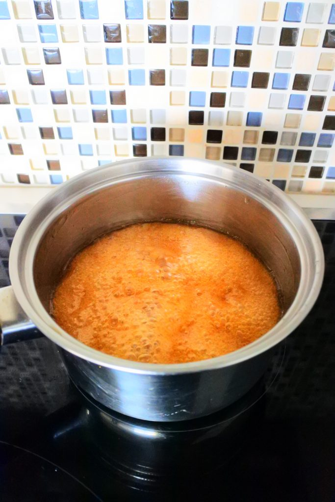 An angled image of a saucepan of simmering ginger candy syrup