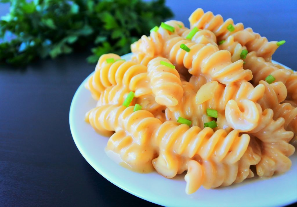 An close up image of gluten free mac and cheese topped with chipped chives