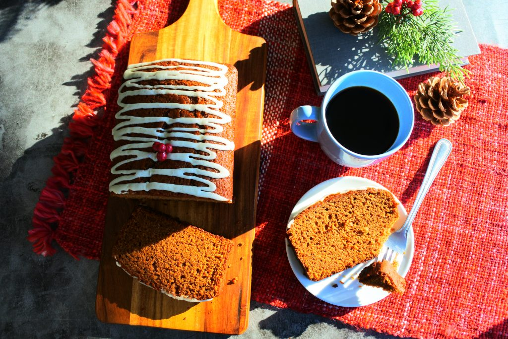 A head on image of a sliced loaf of gingerbread on a wooden board with a slice on a plate with a piece cut out of it next to a teacup and book in the sunlight