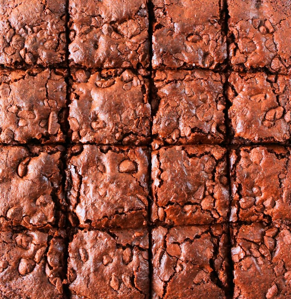 A close up overhead image of a batch of baked chewy gluten free brownies cut into squares