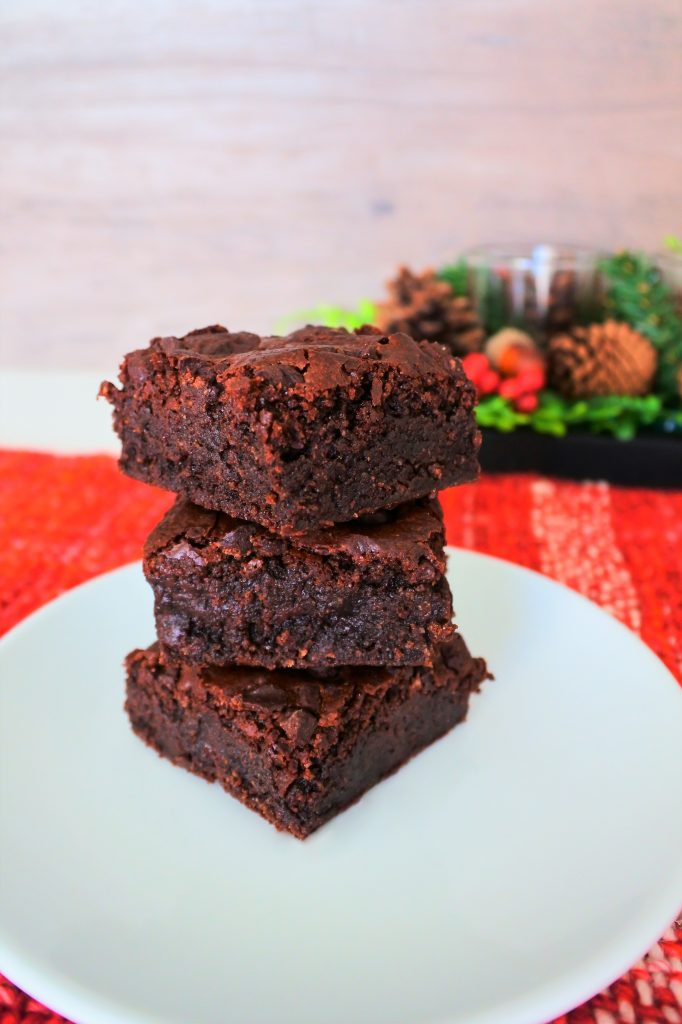 A head on stack of three chewy gluten free brownies on a plate