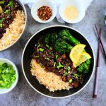 An overhead image of a ground beef teriyaki bowl served with steamed rice, sauteed broccolini and garnished with lemon wedges, chives and sesame seeds