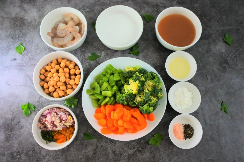 An overhead image of dishes of ingredients for a coconut curry including shrimp, coconut milk, stock, chickpeas, vegetables, herbs and spices, oil, and cornstarch