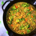 An overhead image of a skillet of shrimp and vegetable coconut curry