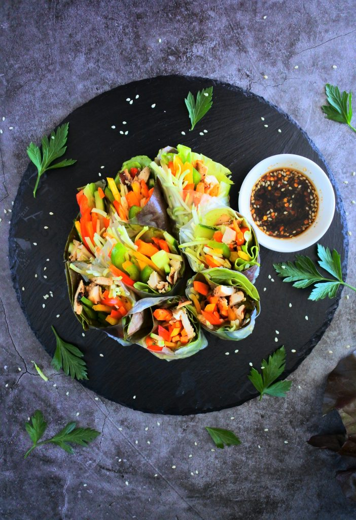 An overhead image of sliced summer rolls on a slate place with a small dish of soy-based dipping sauce