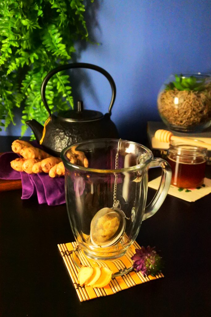A head-on image of an glass mug with a ginger-filled tea strainer with a black kettle, fresh ginger, a small bottle of honey and plants in the background