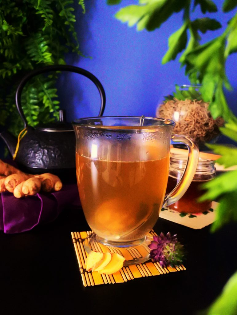 A head-on image of a ginger-tea filled glass mug with a black kettle, fresh ginger, a small bottle of honey and plants in the background