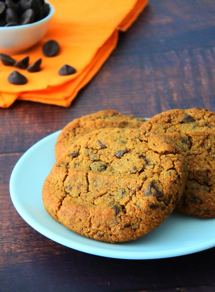 A head on image of a plate of gluten free chocolate chip cookies with a small dish of chocolate chips on an orange cloth napkin in the background