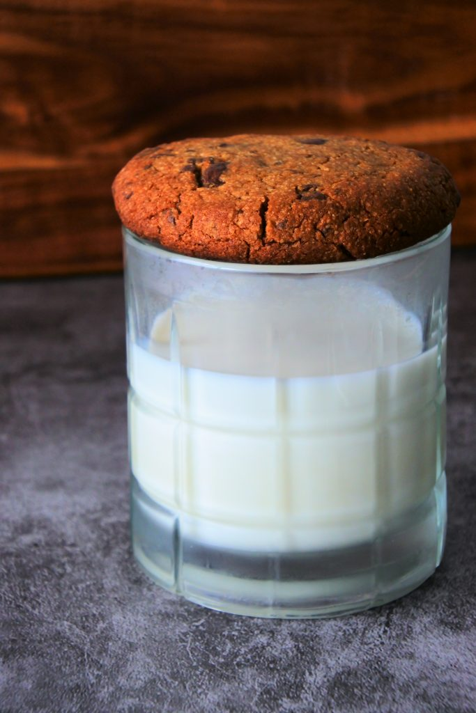 A head on image of a glass of milk with a warm, freshly baked gluten free chocolate chip cookie covering it