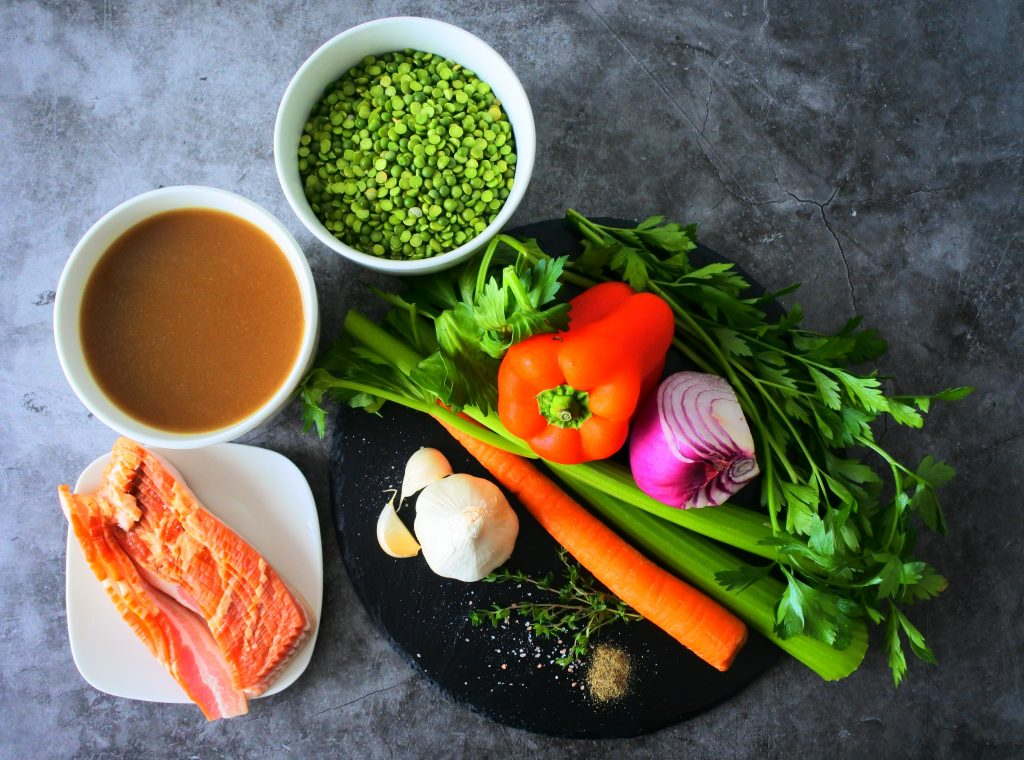 An overhead image of ingredients for a simple split pea and bacon soup including split peas, broth, bacon, and fresh herbs and vegetables