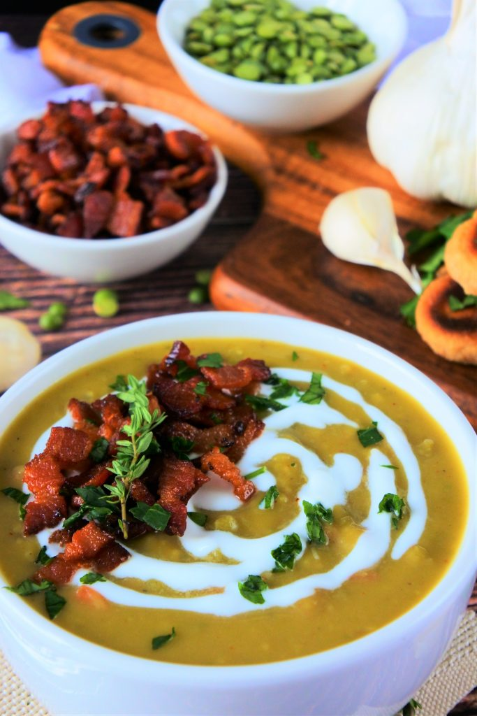 A head on slightly angled image of a bowl of green split pea soup topped with herbs and crispy bacon bits with other fresh ingredients in the background