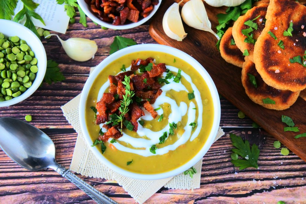 An overhead image of a bowl of green split pea soup topped with herbs and crispy bacon bits with other fresh ingredients surrounding it