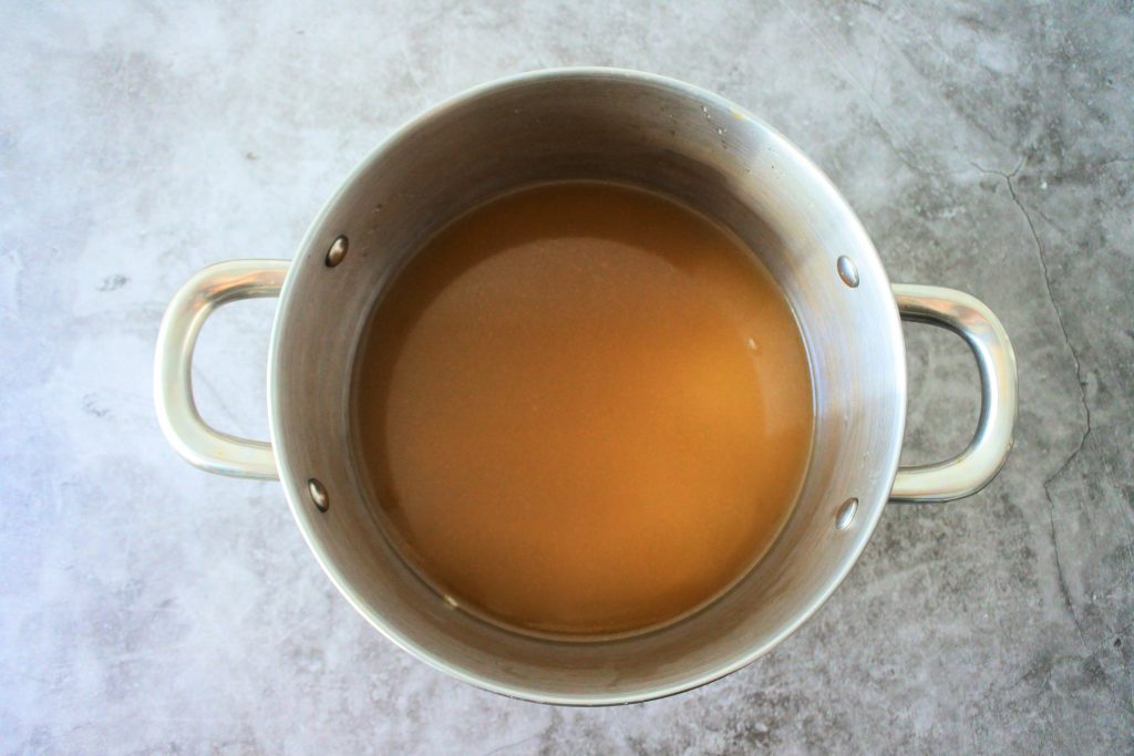 An overhead image of a pot with split peas and broth