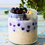 A head on image of a jar of overnight oats topped with wild blueberries