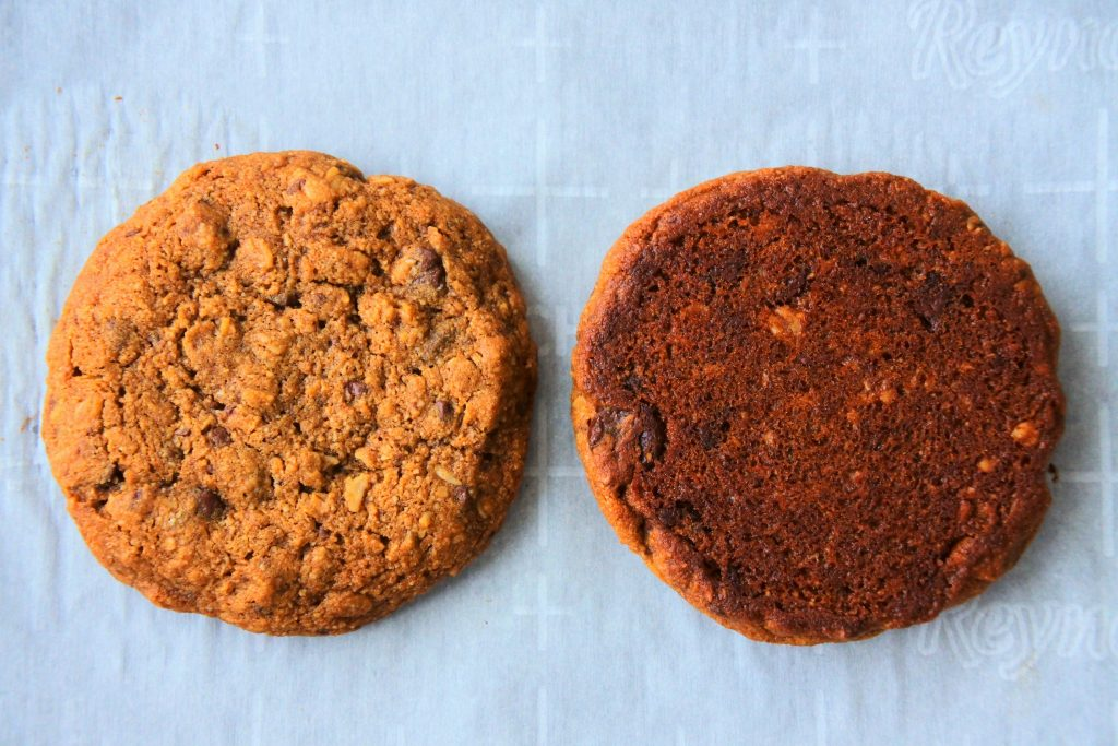 An overhead image of two oatmeal chocolate chip cookies, one face up and one face down