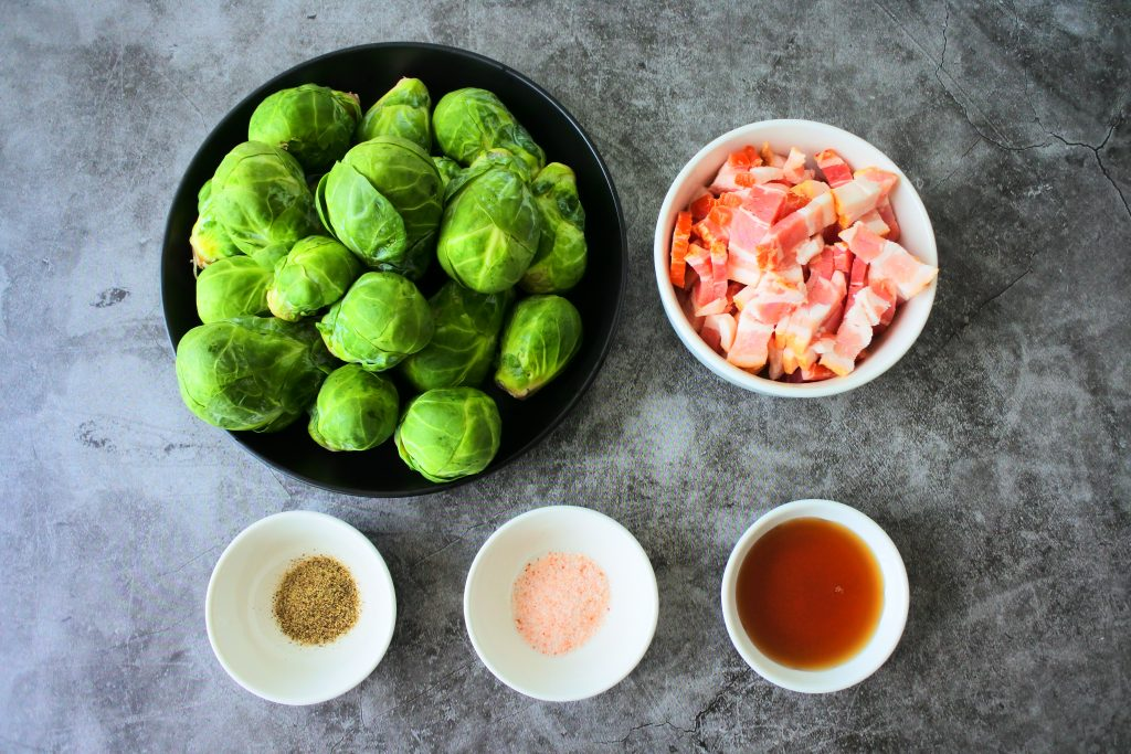 An overhead image of ingredients for maple bacon brussels sprouts including fresh brussels sprouts, diced thick cut bacon, maple syrup, salt and pepper