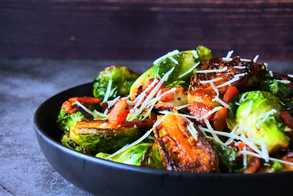 A head on image of a dish of maple bacon brussels sprouts topped with finely shredded cheese