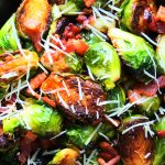 An overhead image of a dish of maple bacon brussels sprouts topped with finely shredded cheese