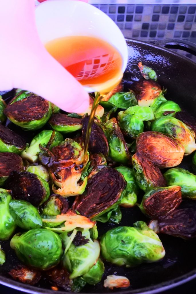 An angled image of a skillet of caramelized brussels sprouts with maple syrup being poured over it.