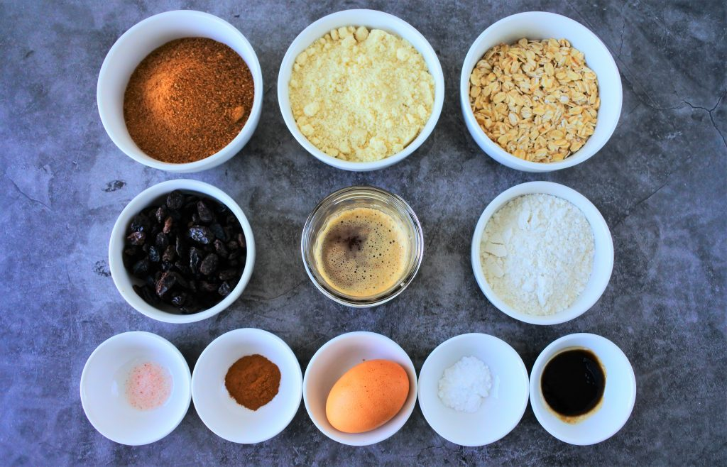 An overhead image of bowls of ingredients for oatmeal raisin cookies