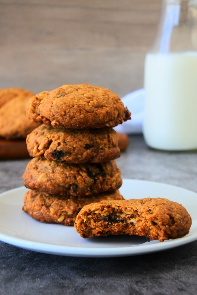 A head on image of freshly baked oatmeal raisin cookies on a plate with a bottle of milk and a pile of cookies in the background
