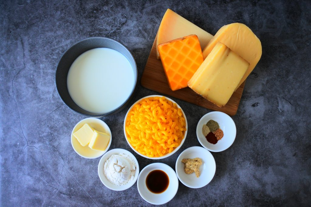 An overhead image of an assortment of ingredients for homemade mac and cheese including whole milk, blocks of cheeses, uncooked pasta, butter, (gluten-free) flour and various spices and seasoning.