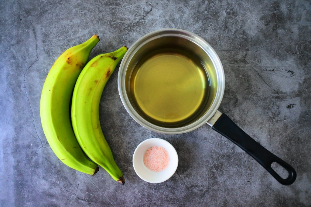 An overhead image of ingredients for fried plantain chips including green plantains, a saucepan of oil and a small dish of salt.