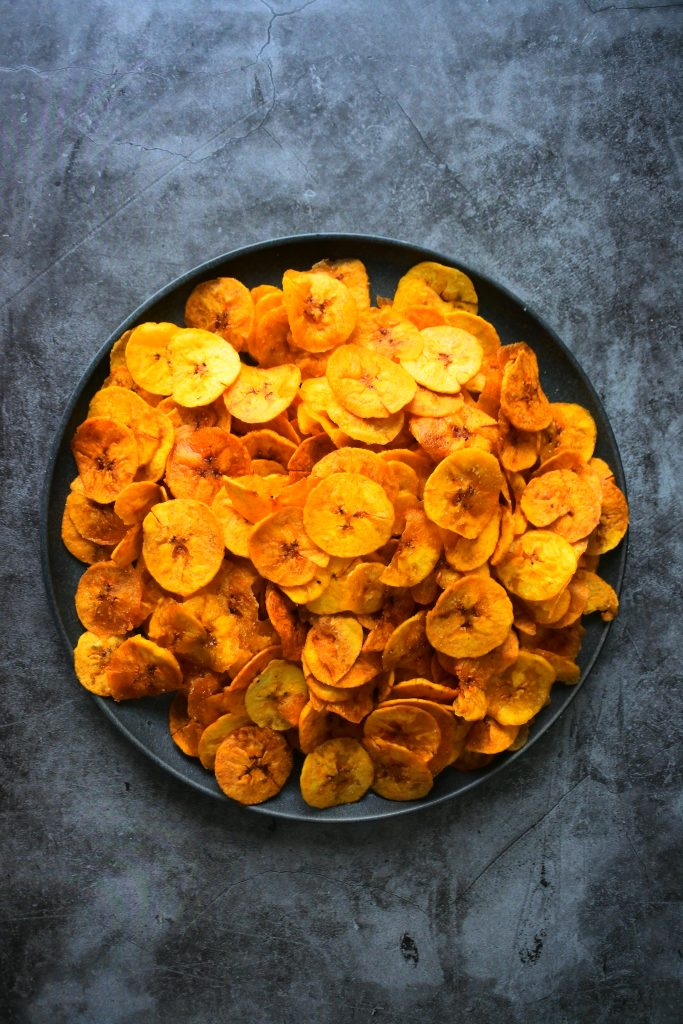 An overhead image of a plate of fresh fried plantain chips