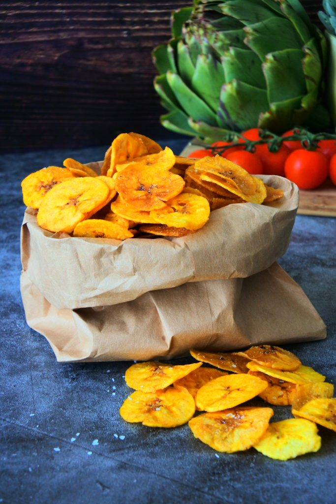 A close up image of a brown paper bag of freshly fried plantain chips dusted with salt.