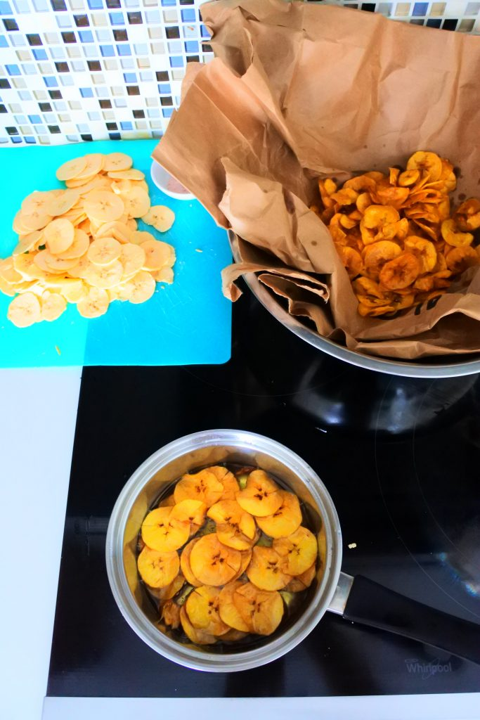 An angled overhead image of the fry station set up for plantain chips including sliced green plantains, a saucepan with oil and chips being fried and a brown paper lined bowl with already fried chips in it