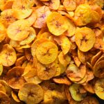 A close up image of freshly fried plantain chips dusted with salt on a plate
