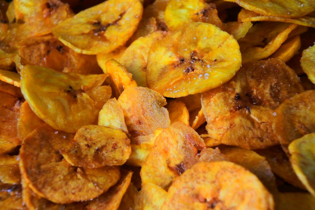 A close up image of freshly fried plantain chips dusted with salt