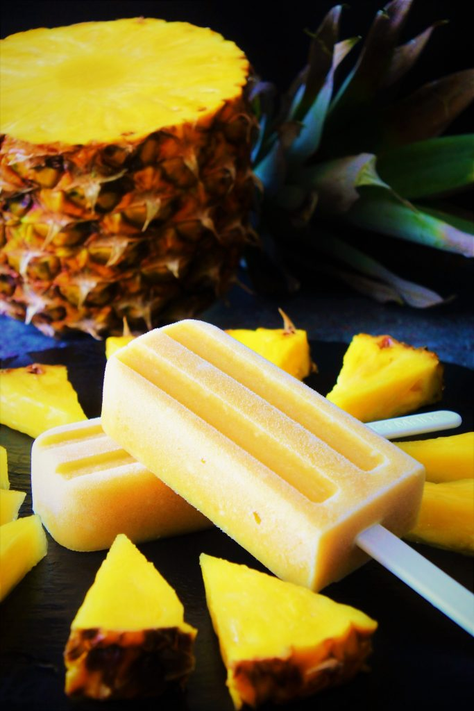 A head on image of two pineapple popsicles surrounded by fresh cut pineapple chunks and half a fresh pineapple in the background