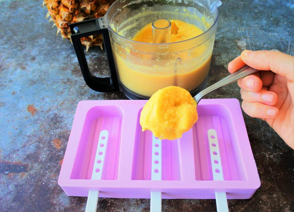 An angled image of a semi-frozen pureed pineapple mixture being spooned into a popsicle mold.
