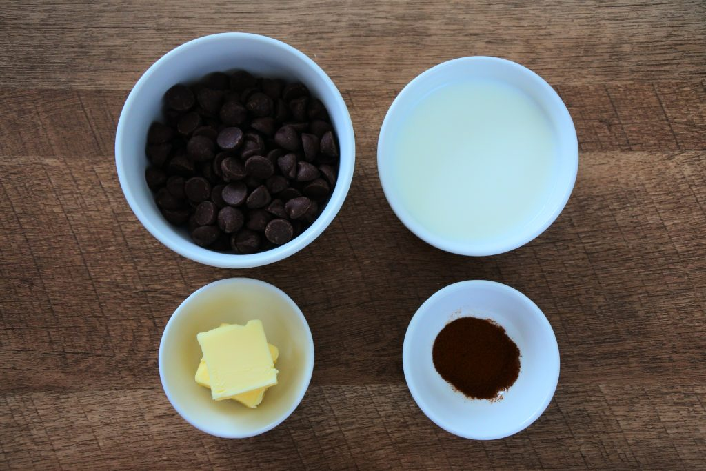 An overhead image of bowls of ingredients for a chocolate ganache frosting
