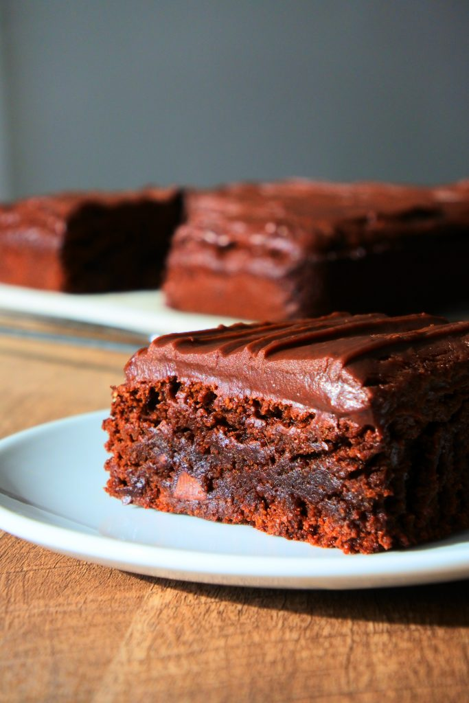 A head on close up image of a slice of chocolate ganache frosted brownie on a plate with a rack with brownies in the background
