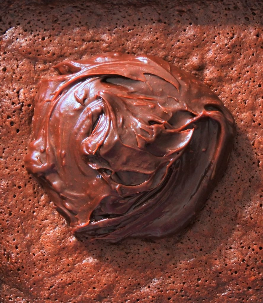 An overhead close up image of chocolate ganache frosting on top of a pan of freshly baked and cooled brownies.