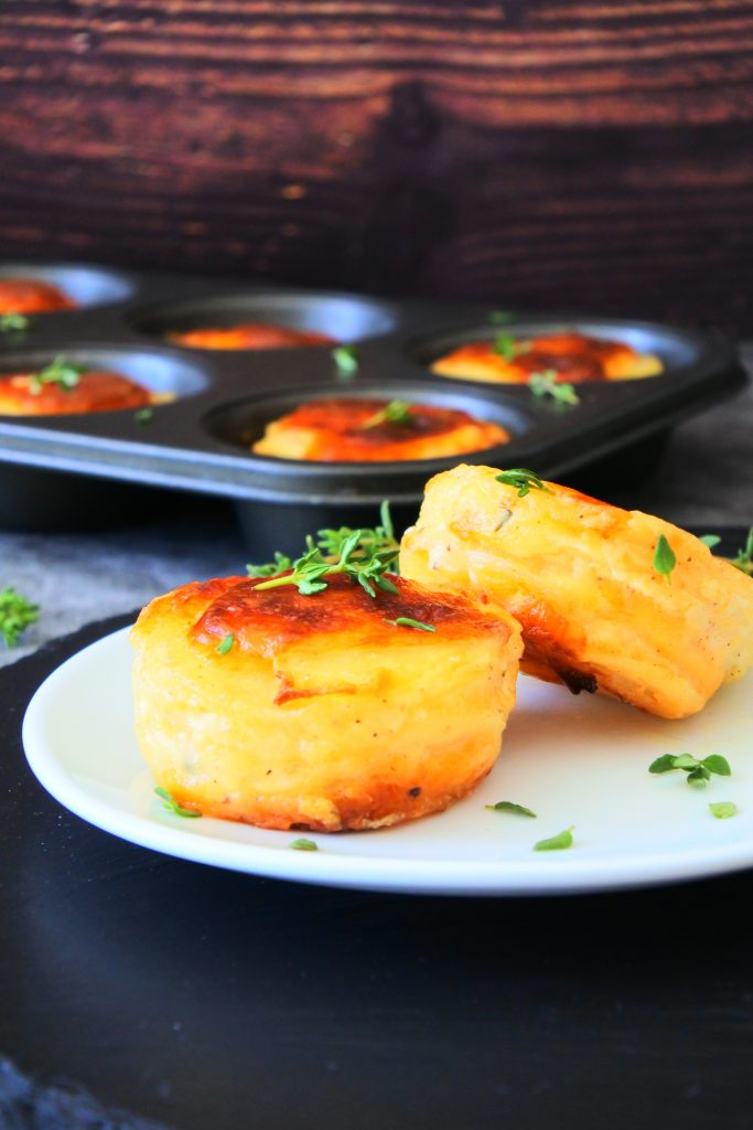 A close up image of two stacks of potato au gratin on a white plate topped with sprigs of fresh thyme with a muffin tin of other stacks in the background