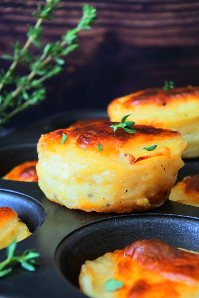 A head on image of a stack of potato au gratin on top of a muffin pan with other individual stacks
