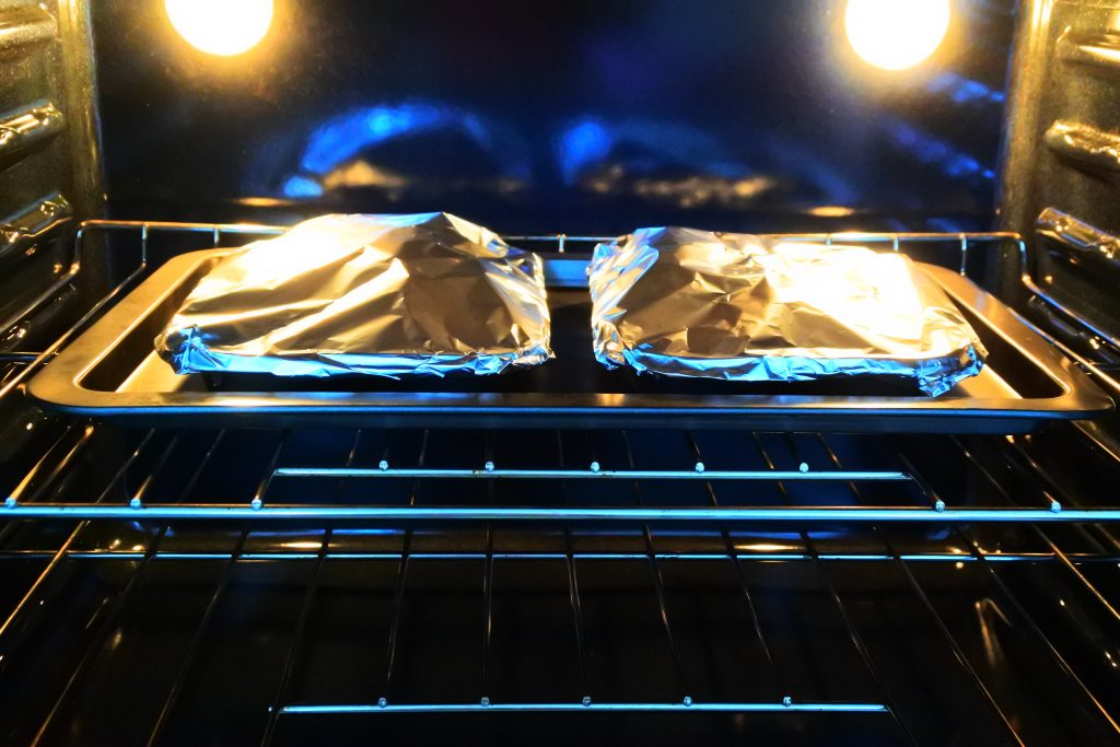 A head on image of a baking tray in the oven with foil tented muffin tins with potato au gratin