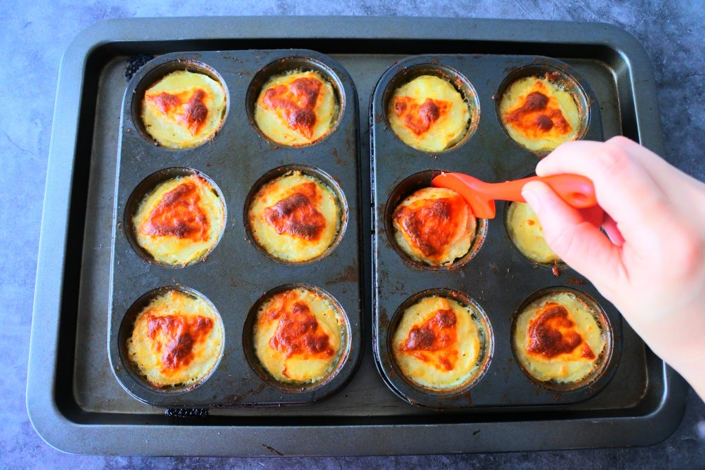 An overhead image of a baking tray with 12 freshly baked potato au gratins in muffin tins with a red silicone spatula being run around the edges to shape them before they cool and set