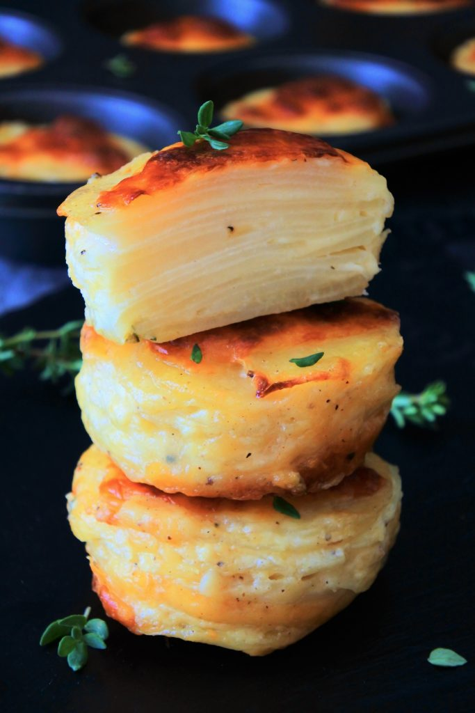A head on image of a stack of three potato au gratins with te top stack being halved to reveal the layers