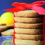 A head on image of a stack of gluten-free lemon shortbread cookies with a red bow wrapped around it