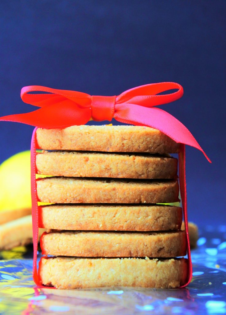 A head on image of a red bow wrapped stack of gluten free lemon shortbread cookies