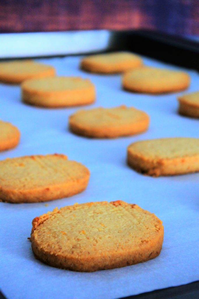 And angled image free lemon shortbread cookies baked and on a parchment lined tray