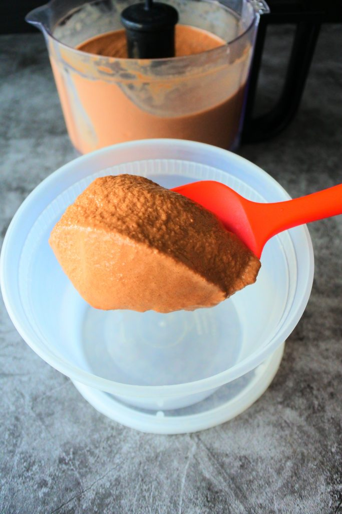 A close up angled image of frozen and blended ice cream base being scooped out a food processor and into a container.
